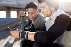 Dos aptos y hombres deportivos del youn que usan el teléfono móvil en la ciudad Imagen de archivo libre de regalías