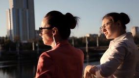 Dos arquitectos de las muchachas hacen una pausa el río y discuten el proyecto de construcción metrajes