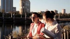 Dos arquitectos de las muchachas hacen una pausa el río y discuten el proyecto de construcción Negocio, construcción almacen de metraje de vídeo