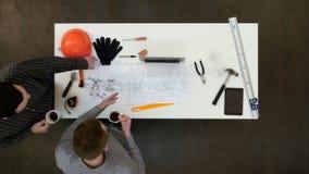 Dos arquitectos de sexo masculino que discuten los modelos que beben el café imagen de archivo