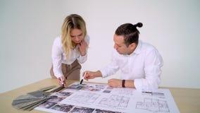Dos arquitectos que discuten plan junto en el escritorio con los modelos almacen de metraje de vídeo