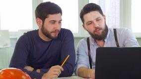 Dos arquitectos que miran la pantalla del ordenador portátil fotografía de archivo