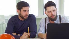 Dos arquitectos que miran la pantalla del ordenador portátil almacen de metraje de vídeo