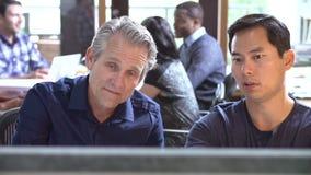 Dos arquitectos que trabajan en el escritorio con la reunión en fondo metrajes
