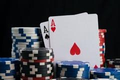 Dos as, primer, rodeado por una apuesta grande en un casino que juega, en un fondo negro fotos de archivo libres de regalías