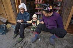 Dos asiáticos y niño año, en umbral de la tienda rural Fotografía de archivo libre de regalías