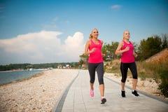 Dos athlets que corren en la playa - verano w de las mujeres de la madrugada Fotos de archivo