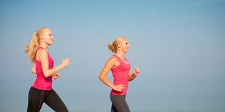 Dos athlets que corren en la playa - verano w de las mujeres de la madrugada Imágenes de archivo libres de regalías
