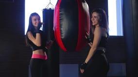 Dos atletas de las muchachas que se colocan cerca de un saco de arena y de una sonrisa