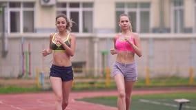 Dos atletas de las mujeres jovenes en la ropa de deportes que corre alrededor del parque Los deportes que entrenan, utilizan un s almacen de metraje de vídeo