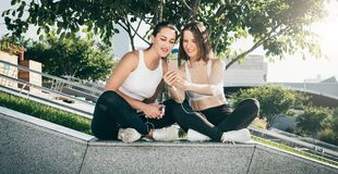 Dos atletas de las mujeres jovenes en ropa de deportes se están sentando en parque, se relajan después de deportes entrenando, ut imagen de archivo