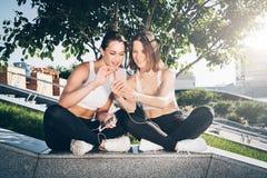 Dos atletas de las mujeres jovenes en ropa de deportes se están sentando en parque, se relajan después de deportes entrenando, ut imágenes de archivo libres de regalías
