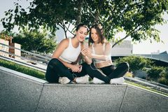 Dos atletas de las mujeres jovenes en ropa de deportes se están sentando en parque, se relajan después de deportes entrenando, ut foto de archivo libre de regalías