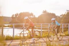 Dos atletas de sexo femenino que montan deportes bikes al aire libre. ima horizontal Fotografía de archivo