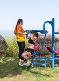 Dos atletas realizan ejercicios en las máquinas públicas al aire libre del ejercicio en el aire abierto en la ciudad de Zefat e fotografía de archivo