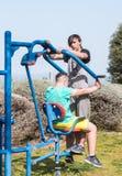 Dos atletas realizan ejercicios en las máquinas públicas al aire libre del ejercicio en el aire abierto en la ciudad de Zefat e fotos de archivo