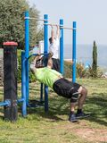 Dos atletas realizan ejercicios en las máquinas públicas al aire libre del ejercicio en el aire abierto en la ciudad de Zefat e imagen de archivo libre de regalías