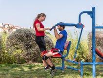 Dos atletas realizan ejercicios en las máquinas públicas al aire libre del ejercicio en el aire abierto en la ciudad de Zefat e fotografía de archivo libre de regalías
