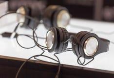 Dos auriculares negros de los pares en la tabla Foto de archivo libre de regalías