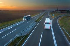 Dos autobuses en la falta de definición de movimiento en la carretera en la puesta del sol Imagen de archivo libre de regalías