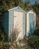 Dos azul que pone en contraste y vertientes pintadas blanco del jardín Foto de archivo libre de regalías