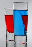 Dos azules y cóctel rojo en vidrio lleno con propias reflexiones Fotos de archivo