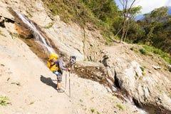 Dos backpackers de los turistas de los hombres que cruzan la cascada fluyen, Bolivia Fotografía de archivo