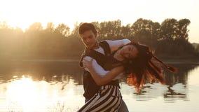 Dos bailarines de los amantes en la puesta del sol Concepto de las danzas del latín y del social metrajes