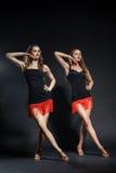 Dos bailarines del cabaret en trajes brillantes sobre oscuridad Fotos de archivo