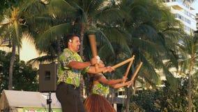 Dos bailarines del hula se realizan en el waikiki con puili almacen de metraje de vídeo