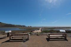 Dos bancos de madera hacen frente a una laguna y a una playa Foto de archivo libre de regalías