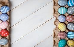 Dos bandejas con los huevos de Pascua coloreados, pintados a mano, están situadas enfrente de uno a en un fondo de madera diagona Imagen de archivo libre de regalías