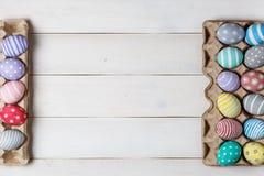 Dos bandejas con los huevos de Pascua coloreados, pintados a mano, están situadas enfrente de uno a en un fondo de madera diagona Imágenes de archivo libres de regalías