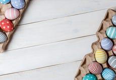 Dos bandejas con los huevos de Pascua hechos a mano coloridos mienten diagonalmente en los bordes enfrente de uno a en la superfi Foto de archivo