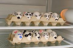 Dos bandejas con sonrisas pintadas en los huevos en el refrigerador dejan de lado Foto de archivo libre de regalías