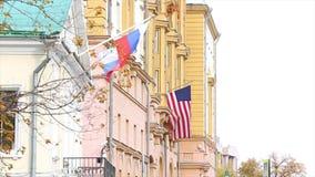 Dos banderas: Ruso y americano, en el edificio de la embajada de América en Rusia almacen de metraje de vídeo