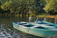Dos barcos con los remos en el lago en una pera de madera en verano cerca del bosque Imagen de archivo libre de regalías
