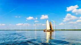 Dos barcos de madera históricos de Botter en vela llena cerca de un parque eólico a lo largo de la orilla de Veluwemeer Fotografía de archivo