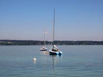 Dos barcos de navegación en el lago azul con el fondo de la montaña Foto de archivo libre de regalías