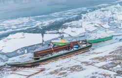 Dos barcos de pesca multicolores atrapados en el río congelado Danubio Imágenes de archivo libres de regalías