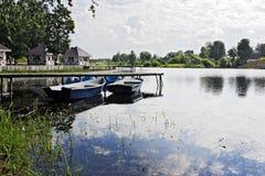 Dos barcos en el embarcadero en el lago Foto de archivo libre de regalías