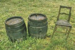 Dos barriles de madera viejos y una silla en el jardín del vinatero imagen de archivo libre de regalías