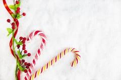 Dos bastones de caramelo con la decoración de la Navidad en el fondo Nevado Imagen de archivo