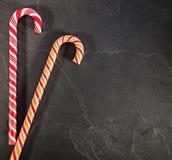 Dos bastones de caramelo en fondo negro Fotos de archivo