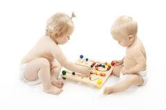 Dos bebés que juegan el fondo del blanco del juego Foto de archivo