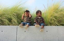Dos bebés que se sientan en una repisa imagenes de archivo