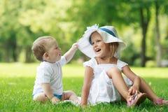 Dos bebés se están sentando en la hierba foto de archivo