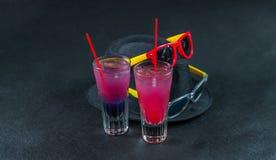 Dos bebidas coloreadas, una combinación de azul marino con púrpura, Fotos de archivo