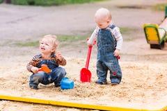 Dos bebés que juegan con la arena Fotografía de archivo libre de regalías