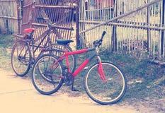 Dos bicicletas cerca de la cerca vieja en pueblo Imagen de archivo